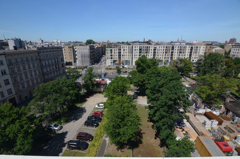 Teren przed budynkiem MINI apartamentów wypełnia zieleń, a odległość do ul. Pułaskiego to ponad 80 m